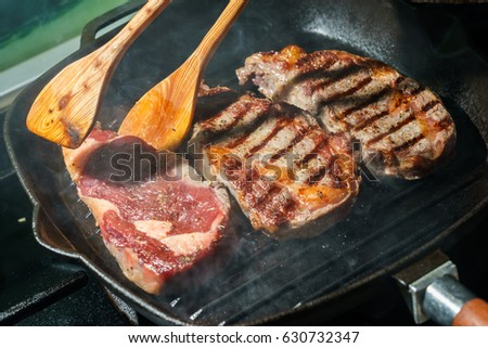 Raw Ribeye Steak with Herbs and Spices, frying on grill pan