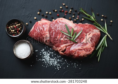 Raw ribeye steak with seasonings over black wooden surface, close-up - stock photo