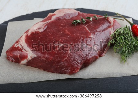 Raw ribeye steak with thyme and dill on wood background