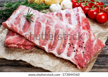 Raw ribs with a rosemary and vegetables. on crumpled paper - stock photo
