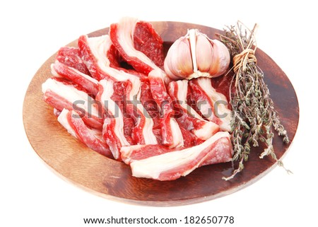 raw ribs with thyme and garlic on wooden isolated over white background - stock photo
