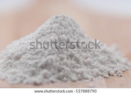 Raw rice and flour in spoon on wooden background.