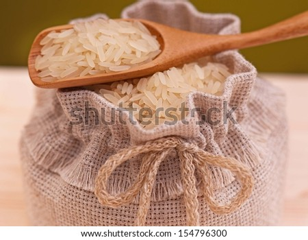 Raw rice in a burlap with wooden spoon close-up - stock photo