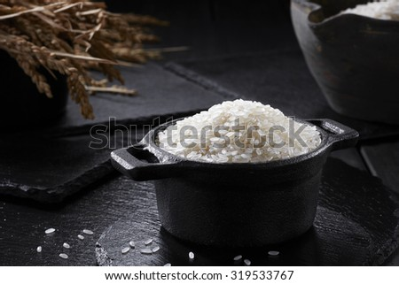 Raw rice in a pot on black background