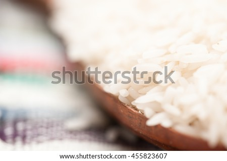 Raw rice in spoon on napkin and wood background