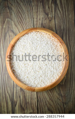 Raw rice in wooden bowl on wooden background. - stock photo