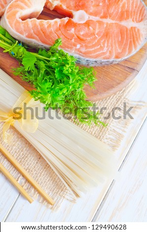 raw rice noodles and raw salmon - stock photo