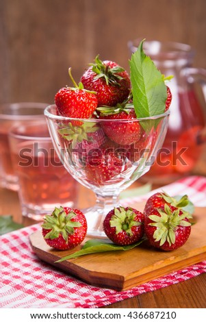 raw ripe fresh srrawberry in glass container with compote in studio - stock photo