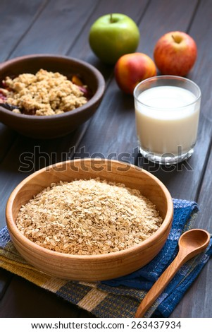 Raw rolled oats in wooden bowl with fruits, glass of milk and a bowl of fruit crumble in the back, photographed on dark wood with natural light (Selective Focus, Focus one third into the oats) - stock photo