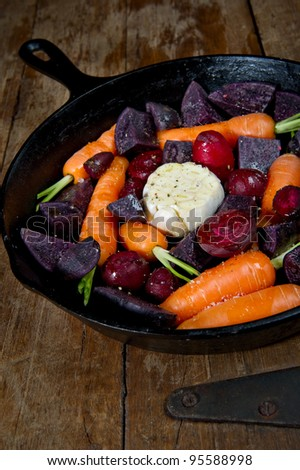 Raw root vegetables in a cast iron skillet ready for the oven and shot from above. Vegetables include carrots, red beets, garlic and purple potatoes. - stock photo