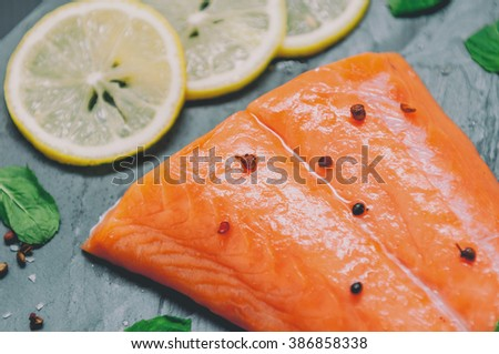 Raw Salmon and ingredientsfor cooking on a dark background