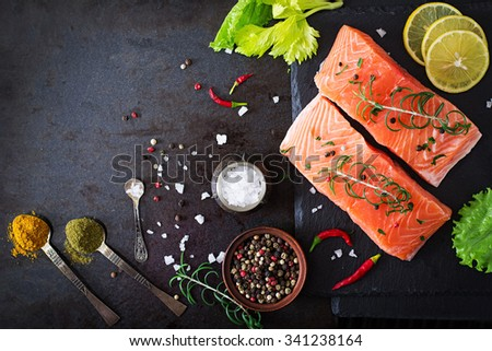 Raw salmon fillet and ingredients for cooking on a dark background in a rustic style. Top view - stock photo