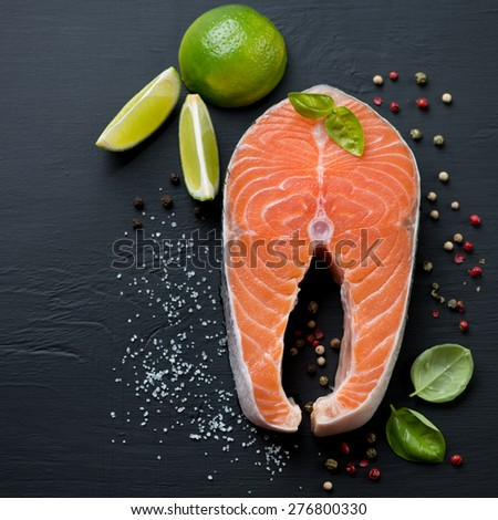 Raw salmon fillet over black wooden background, above view - stock photo