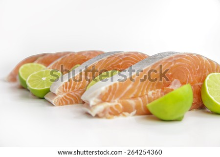 raw salmon fillet with half a lime - stock photo