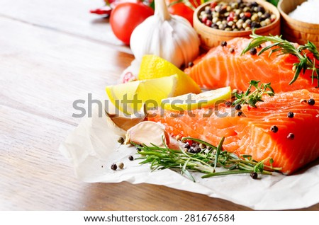Raw salmon fillet with rosemary pepper sweetbread and salt on baking paper rustic theme with copy-space - stock photo