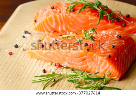 Raw salmon fillet with rosemary pepper thymus and salt on wooden cutting board
