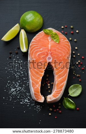 Raw salmon fillet with seasonings over black wooden background, above view - stock photo