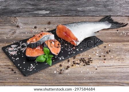 Raw salmon fish steaks on cutting board - stock photo