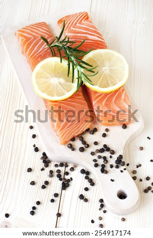 Raw salmon fish steaks with fresh herbs on cutting board - stock photo