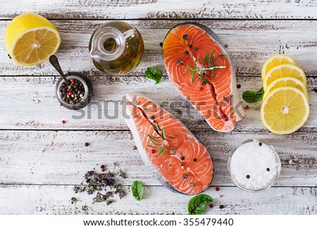 Raw salmon steak and vegetables for cooking on a light wooden background in a rustic style. Top view - stock photo