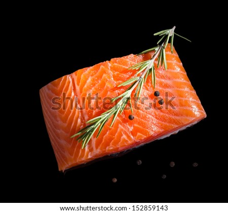 Raw salmon steak isolated on black background with reflection.