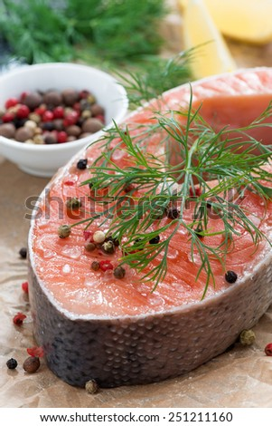 raw salmon steak, lemon and spices prepared for cooking, close-up, vertical - stock photo