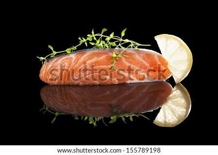 Raw salmon steak with lemon and fresh herbs isolated on black with reflection. Healthy seafood eating.  - stock photo