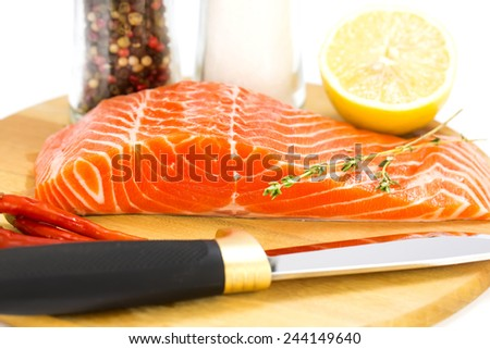 raw salmon steak with lemon and spices on a cutting board - stock photo