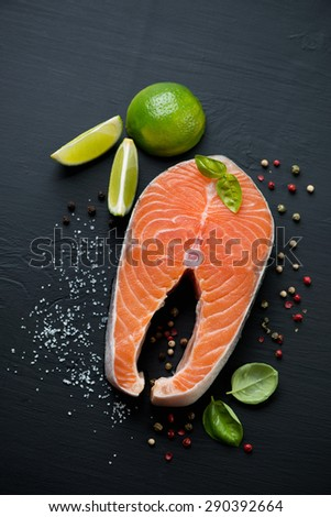 Raw salmon steak with seasonings, black wooden surface, top view - stock photo