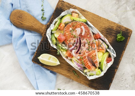 Raw salmon steak with veggies in a foil boat, ready for baking. Copy space - stock photo