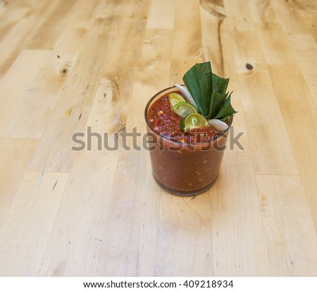 Raw sambal or hot chili sauce in clear glass and garnished with slices of limes and folded banana leaf for decoration. - stock photo