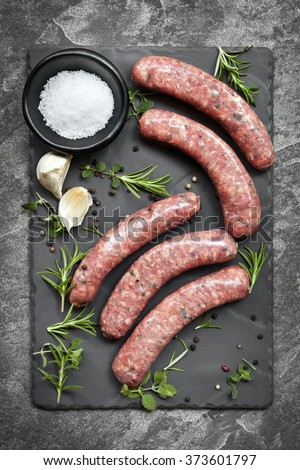 Raw sausages on slate, with herbs and spices.  Overhead view.