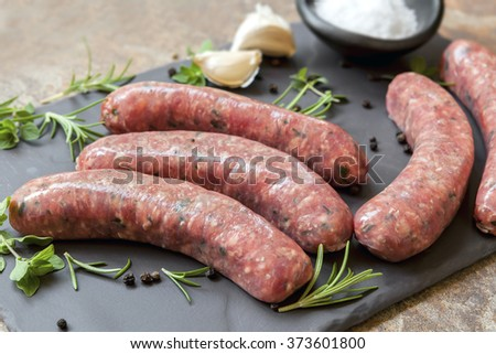 Raw sausages on slate, with herbs and spices. Side view. - stock photo