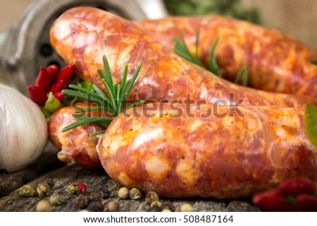 Raw sausages with rosemary, garlic and peppercorn with meat grinder in the background