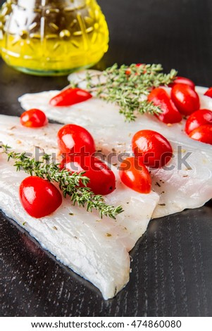 Raw sea bass fillets with cherry tomatoes on black wood