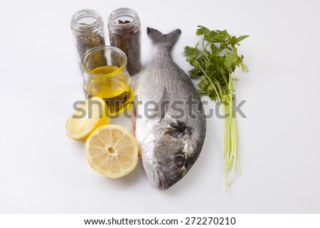 Raw sea bream fish with some ingredients. Isolated over white background - stock photo