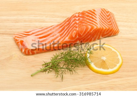 Raw sea trout fillet with fennel and lemon on a wooden board - stock photo