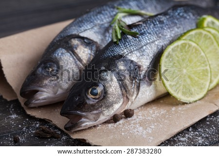 Raw seabass fish on the wooden board with vegetables - stock photo