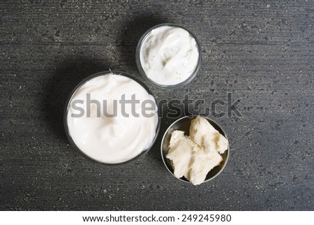 raw shea butter and moisturizers on dark wooden table