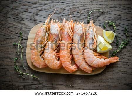 Raw shrimps with lemon wedges - stock photo