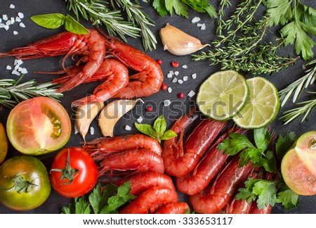 Raw shrimps with tomatoes,  lime and herbs over dark background