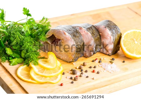 raw sliced steak of sturgeon fish with greens, lemon, different peppers and salt, isolated on white background, closeup - stock photo