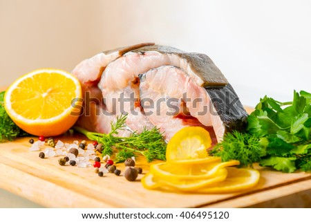 raw sliced steak of sturgeon fish with greens, lemon, different peppers and salt on wooden background, close up - stock photo