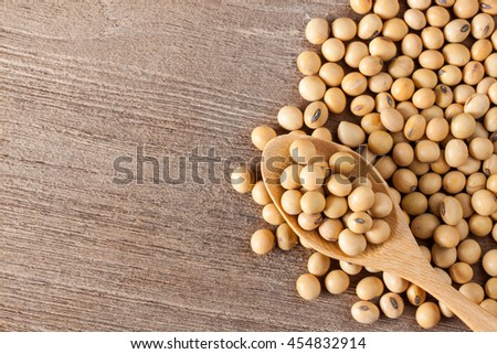 Raw soy beans in a spoon on a wooden table, top view background - stock photo