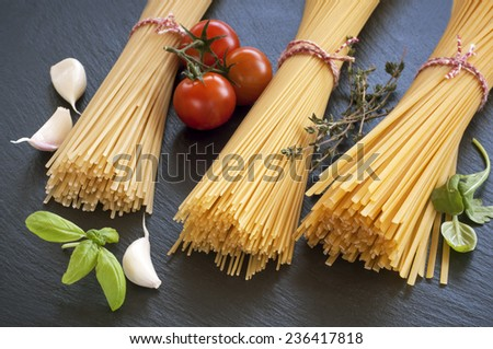 Raw spaghetti with cherry tomatoes , garlic and  herbs - stock photo