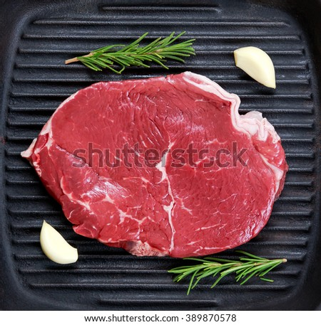 raw steak in iron grilled pan with herb.