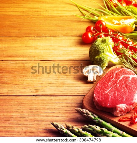 Raw steak on the wooden board.Filtered image: warm cross processed vintage effect. - stock photo