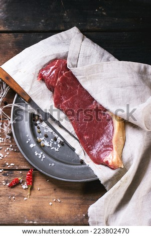 Raw steak on vintage metal plate over old wooden table. See series