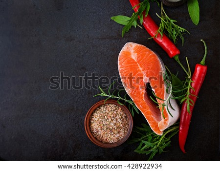Raw steak salmon and vegetables for cooking on a black background. Dietary menu. Proper nutrition. Top view - stock photo