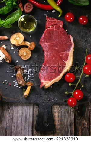Raw steak served with vegetables and forest mushrooms on black metal cutting board over old wooden table.  - stock photo